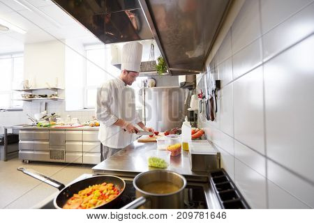 cooking food, profession and people concept - male chef cook with knife chopping tomatoes on cutting board at restaurant kitchen