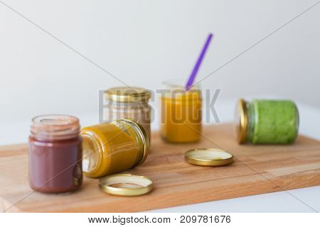 baby food, healthy eating and nutrition concept - vegetable or fruit puree in glass jars and feeding spoon on wooden board