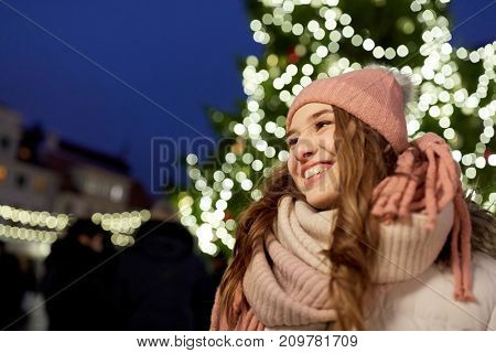holidays and people concept - portrait of beautiful happy young woman at christmas tree in winter evening