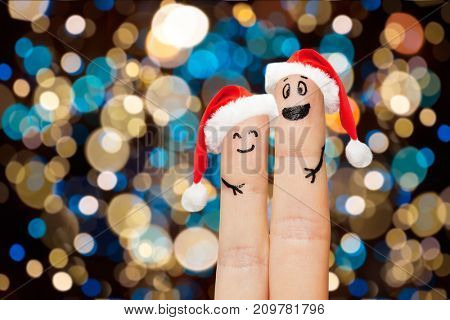 christmas, holidays and body parts concept - close up of two fingers in santa hats with smiley faces over lights background