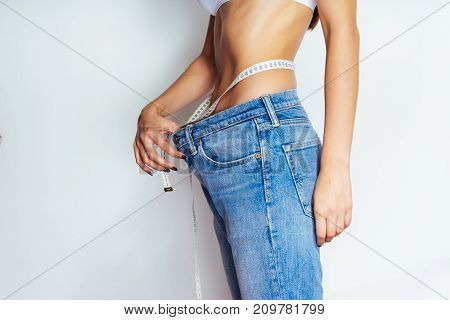 young girl shows how much thin, blue jeans have become big