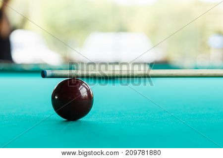 A dark red ball on the green leaf of the table against the background of a blurred pyramid with cue