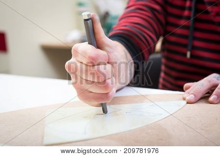 Men's Hands Cut Glass On The Stencil With A Metal Glass Cutter
