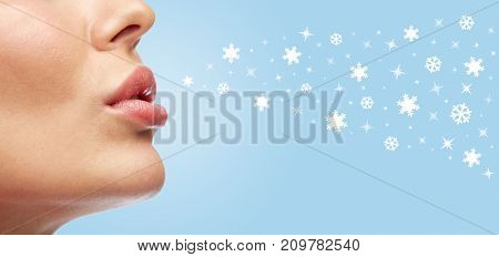 beauty and makeup concept - closeup of young woman lips with snowflakes over blue background