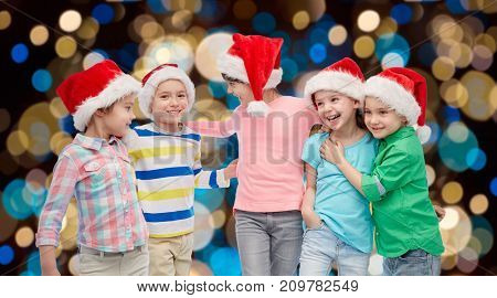 childhood, holidays, friendship and people concept - group of happy smiling little children in santa hats hugging over christmas lights background