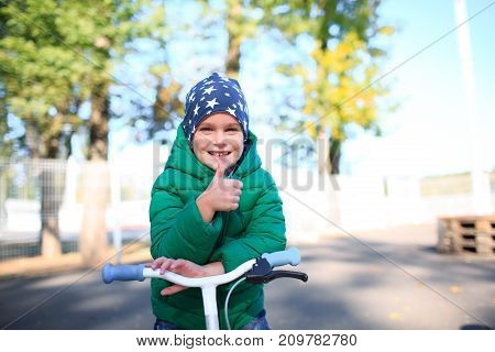 child on a bicycle at asphalt road in the park