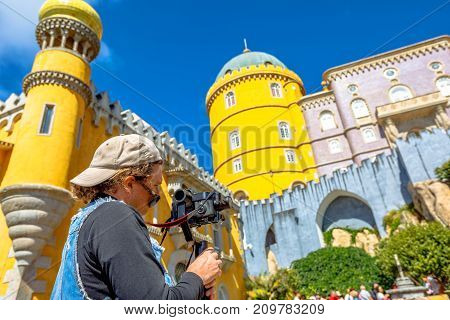 Operator while working with a professional camera with stabilizer. Video photographer shoots clips of famous Pena National Palace in Sintra, Portugal. Photographer traveling in Europe.