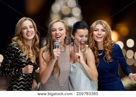 holidays and people concept - happy women with microphone singing karaoke at new year party over christmas tree lights background