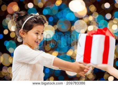 holidays, childhood and people concept - smiling little girl giving or receiving present over lights background