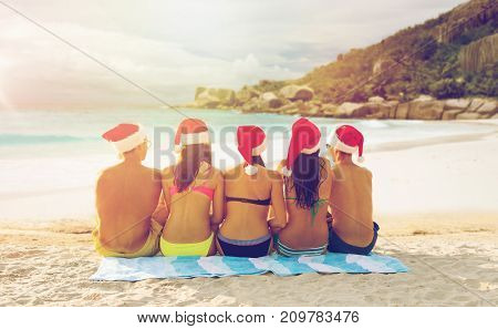 christmas, travel, winter holidays and people concept - group of friends in santa helper hats sitting over tropical island beach background