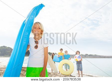 Blond cute kid with friends on sandy beach holding blue swimming matrass