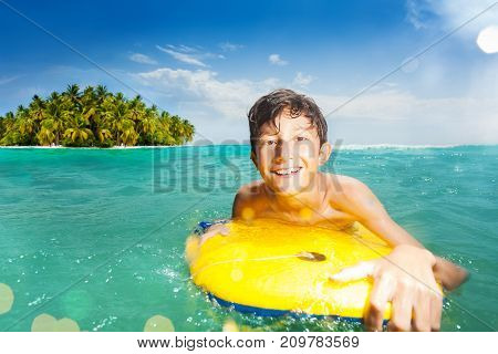 Handsome boy swim in the sea on body board and tropical island on background