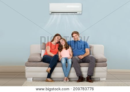 Happy Family Sitting On Sofa Under Air Conditioning At Home
