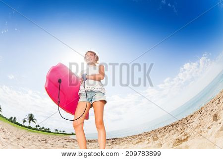 Confident teenage girl standing on the palm beach with pink body board ready to swim