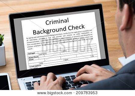 Man Filling Criminal Background Check Application Form On Laptop In Office