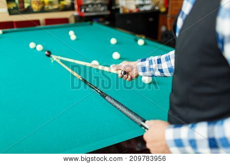 The player broke the pyramid from the balls and is going to make the next blow with the cue stand