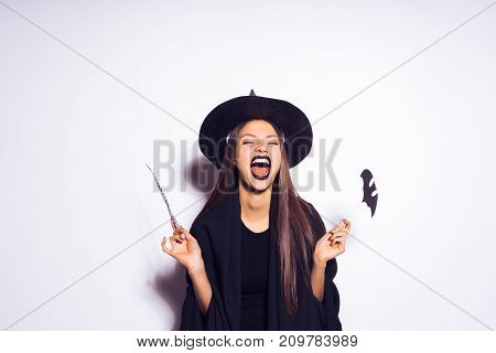 young sexy gothic girl dressed in a witch for Halloween, standing in a big black hat, holding a magic wand and laughing