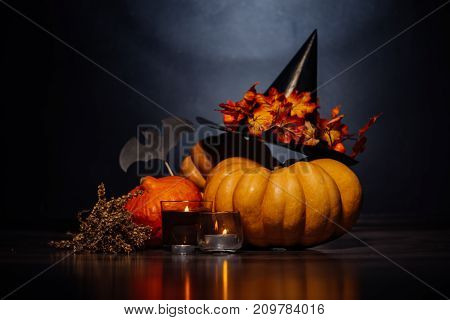 a composition for decorating a house for halloween, lie yellow and orange pumpkins, burning scented candles, a large black witch hat