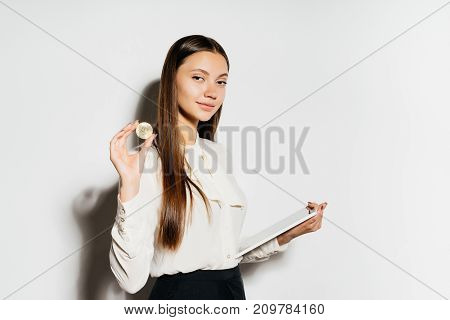 a young modern successful girl holds a gold bitcoin and securities