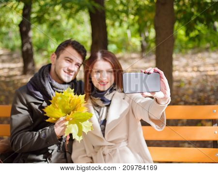 Young couple in love siting on bench in a park on a sunny autumn day and selfing