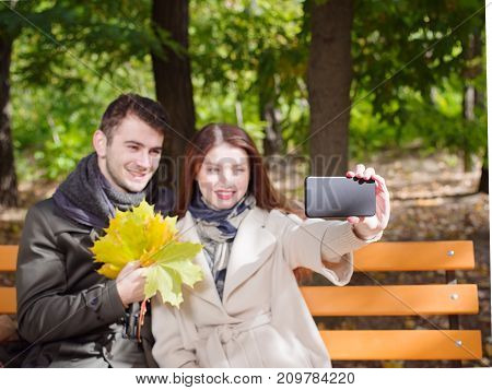 Photo of young couple in love siting on bench in a park on a sunny autumn day and selfing