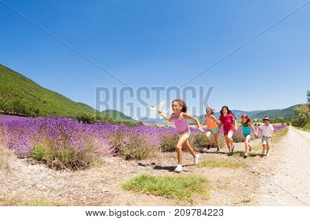Big group of happy age-diverse kids running with toy airplane through lavender field  in summer Provence