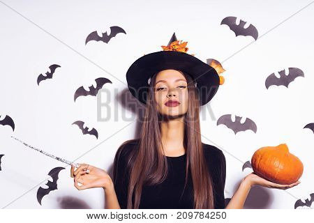 a young sexy gothic girl dressed in a witch for Halloween, standing in a big black hat, holding a magic wand and a pumpkin