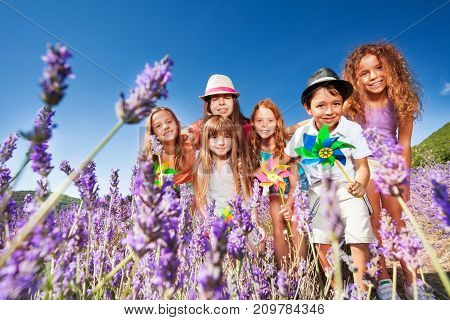 Low-angle shot of happy preteen boys and girls standing in lavender field with colorful pinwheels, looking at camera