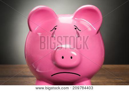 Close-up Of A Sad Pink Piggybank Against Grey Background