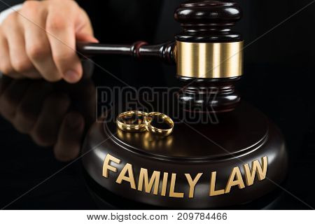 Close-up Of Judges' Hand Hitting Gavel With Golden Rings And Family Law Text At Desk