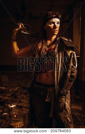 Pretty post apocaliptic girl with steel hand and gun posing in a ruined house