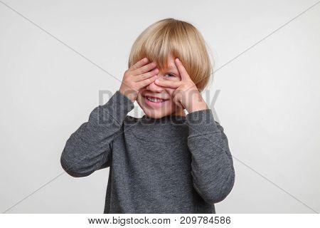 Emotional portrait of caucasian boy. Handsome happy child, photo on grey background