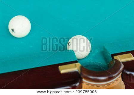 The white ball on the green canvas falls into the billow of the table in good light and the second ball fought back