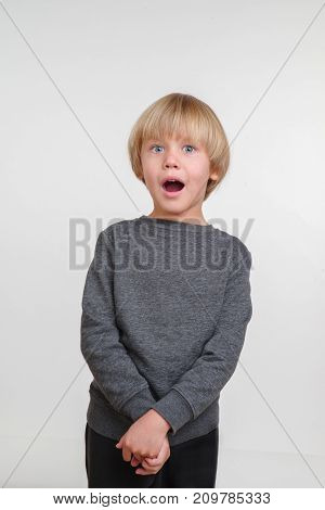 Cool vertical portrait of handsome happy child, photo on grey background