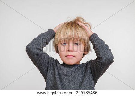 Fine horisontal portrait of handsome happy child, photo on grey background
