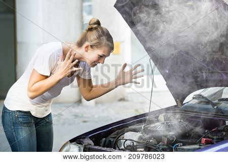 Frustrated Young Woman Looking Under The Hood Of Breakdown Car