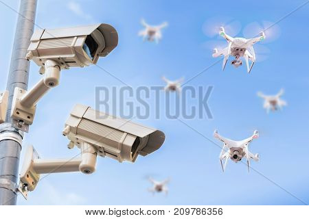 Surveillance Cameras On Pole With Drones Flying In The Blue Sky