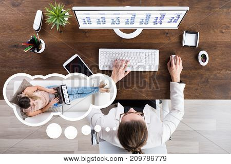 Young Businesswoman In Office Imagining To Do Work On Laptop At Home