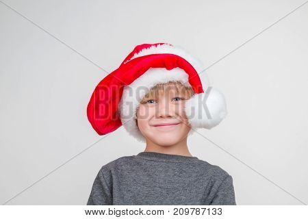 Emotional portrait of caucasian boy vith santa hat
