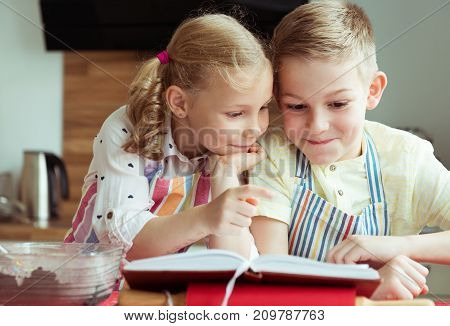 Two Beautiful And Happy Children Exploring Recept Before Preparing Christmas Cookies