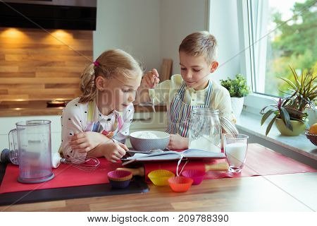 Two Happy Little And Cute Children Preparing Muffins In Modern Kitchen