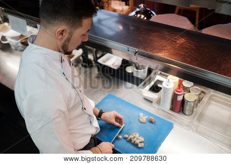 Chef is cutting raw shrimp with big special knife. Culinary seafood cooking.