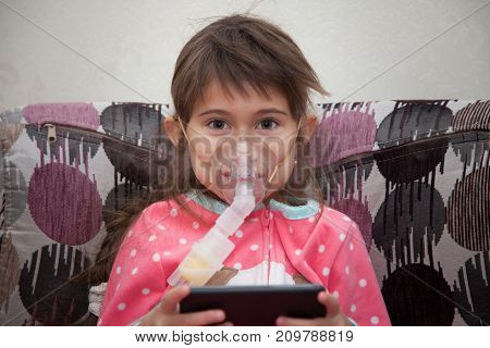 Little girl is wearing a breathing mask and playing games on mobile phone	She is sick. Girl is inhaling medicine through inhaler at home. She dressed in dotted pink pajamas. Her disease is pneumonia.