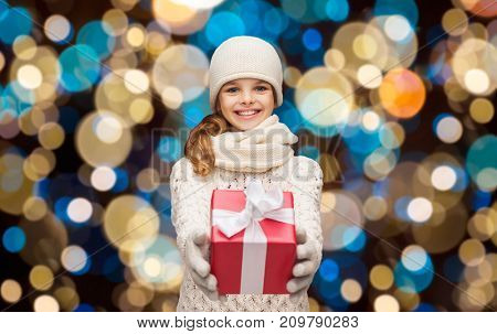 christmas, holidays and people concept - happy girl in winter clothes with gift box over lights background