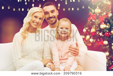family, christmas, holidays and people concept - happy mother, father and little daughter sitting on sofa over lights background
