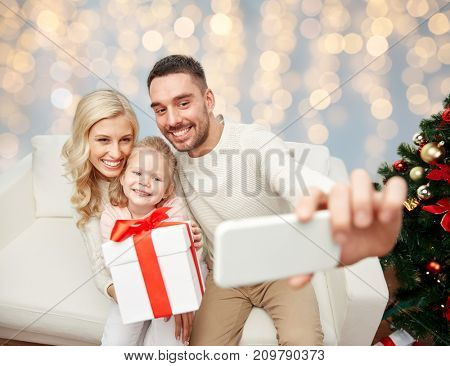 christmas, holidays, technology and people concept - happy family sitting on sofa and taking selfie picture with smartphone over lights background