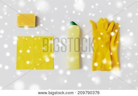 cleaning stuff, housework, housekeeping and household concept - bottle of detergent, rubber gloves with rag and sponge on white background over snow