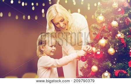 family, winter holidays and people concept - happy mother and little daughter decorating christmas tree