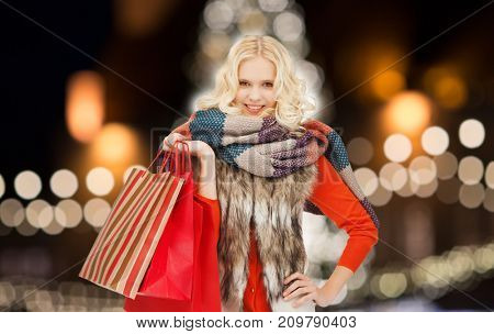 sale, holidays and people concept - happy teenage girl or young woman in winter clothes with shopping bags over christmas tree lights background