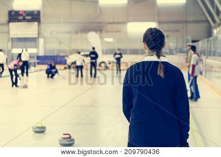 Playing a game of curling. Player preparing for throw.
